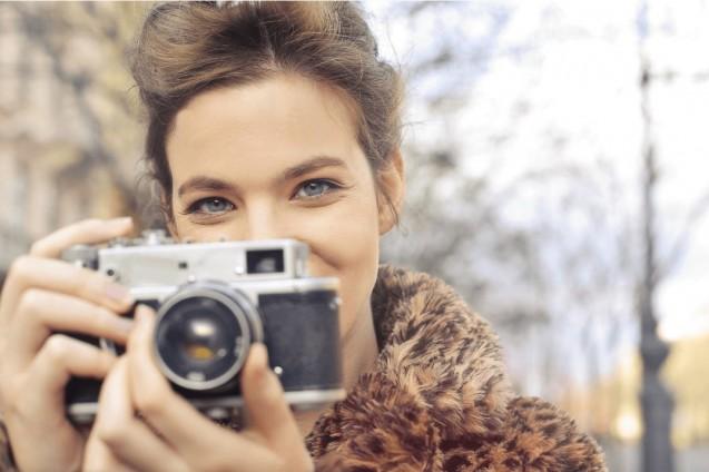 Dzień. Plener. Uśmiechnięta kobieta trzyma przy twarzy aparat fotograficzny.