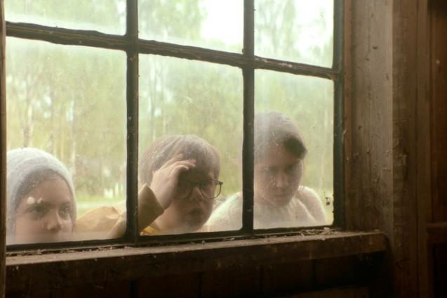 Dwójka dzieci zagląda przez okno do wnętrza budynku.