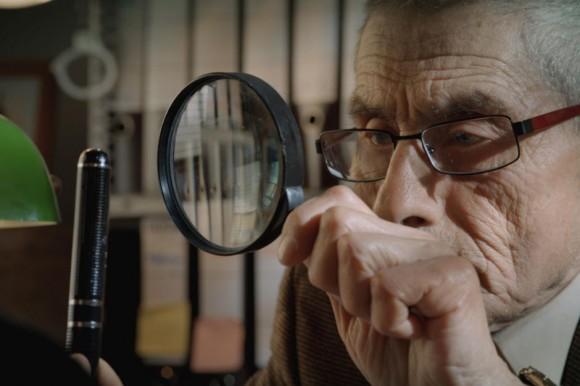 Starszy mężczyzna ogląda pióro przez lupę.