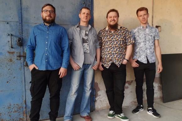 Czterech uśmiechniętych mężczyzn w koszulach i jeansach stoi na tle ściany. Uśmiechają się.