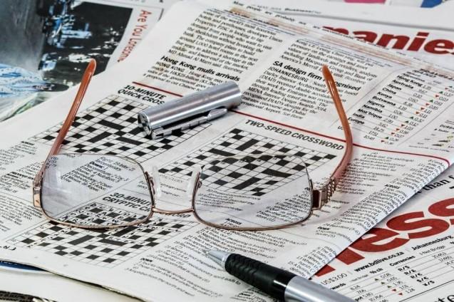 Gazeta z krzyzówką. Na gazecie leżą okulary i otwarty długopis.