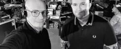 Dwóch mężczyzn w studiu nagraniowym. Jeden z nich ma słuchawki na uszach.