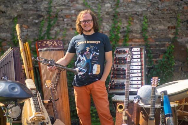 Uśmiechnięty mężczyzna trzyma trąbkę. Otoczony jest wieloma instrumentami.