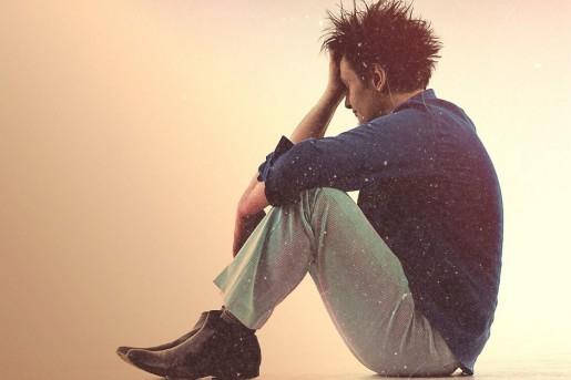 Młody mężczyzna siedzący w kucki, podpierający głowę. Białe tło.
