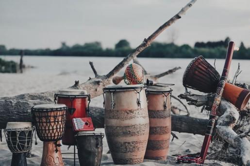 Krajobraz z rzeką. Na brzegu ustawione są różne instrumenty.